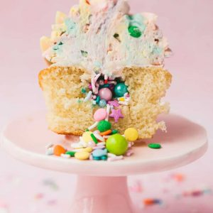 A cupcake cut in half with sprinkles cascading out from it