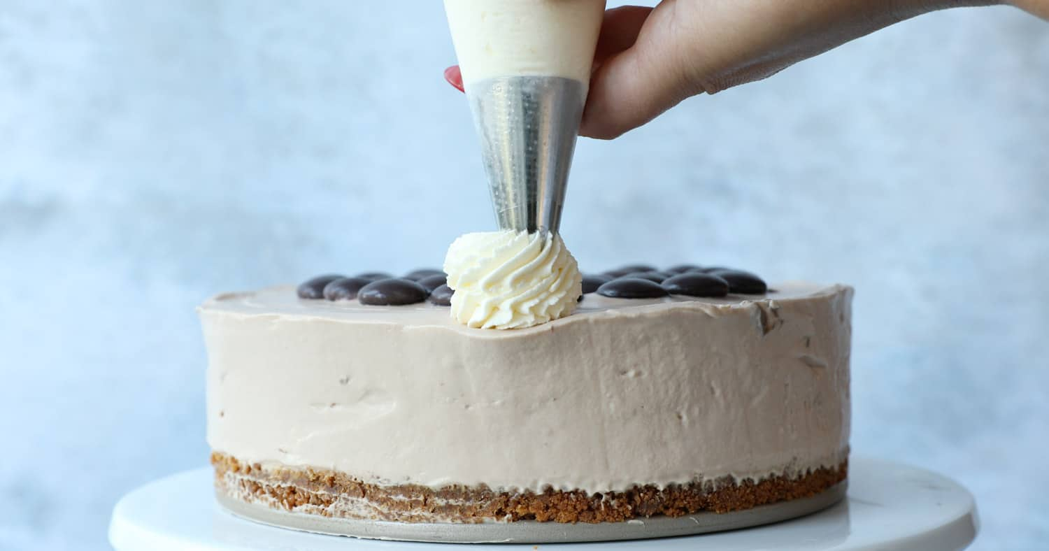 Side view of cream swirls on a Galaxy Caramel Cheesecake being piped with a Wilton 8B piping tip.