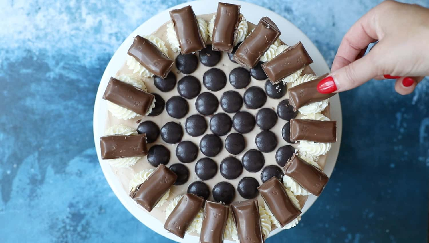 Overhead view of a cheesecake. There is a spiral of Minstrels in the middle surrounded by cream swirls. There is a piece of Galaxy Caramel chocolate on top each swirl.
