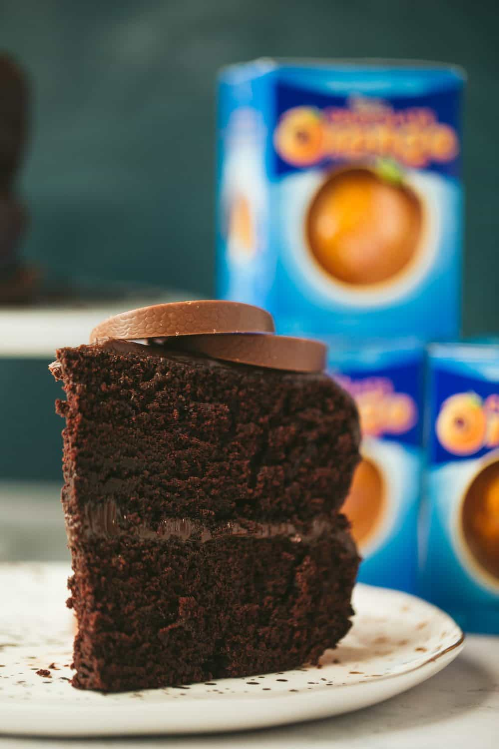 A slice of chocolate orange cake topped with Terry's chocolate orange segments. There are 3 boxes of chocolate oranges visible in the background.