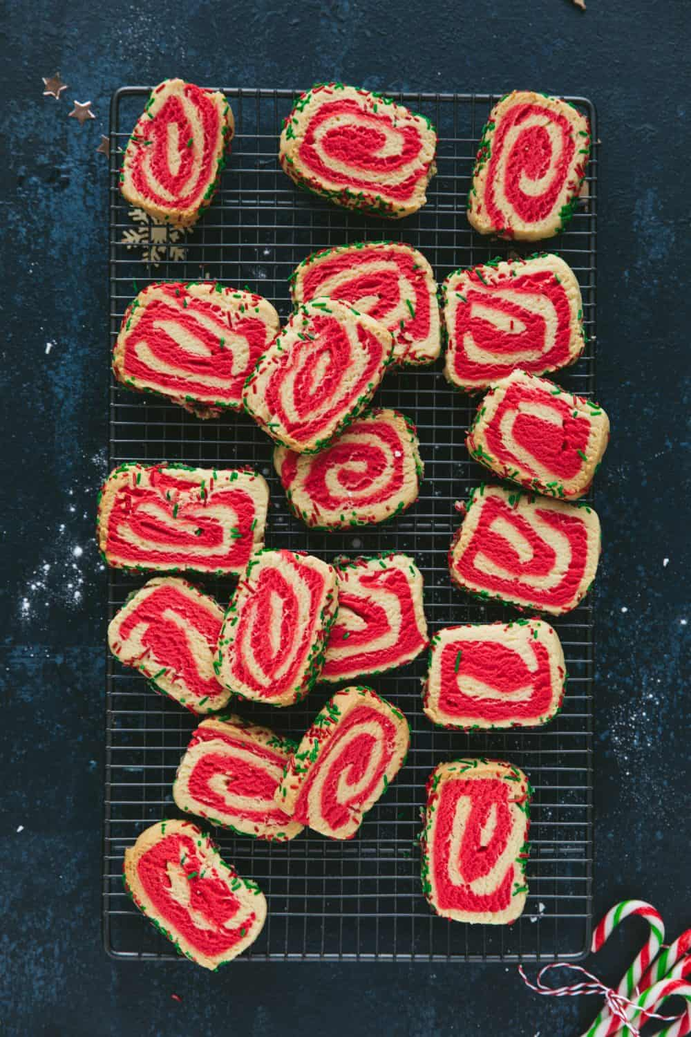 Red and white swirl biscuits on a baking rack.