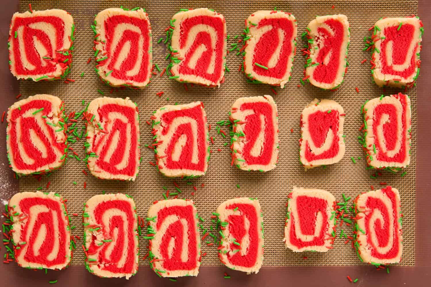 18 red and white vanilla swirl biscuits.