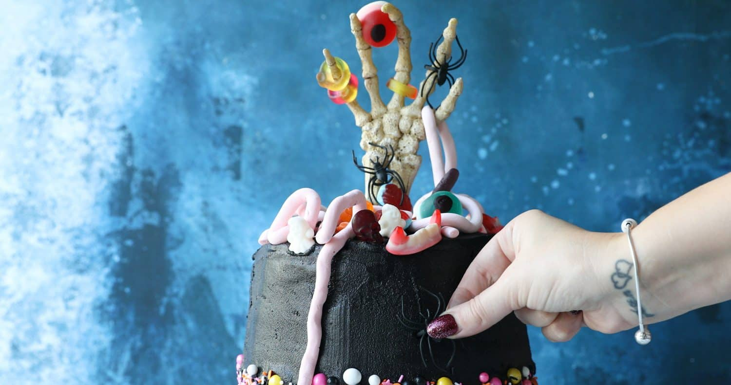Pressing a black plastic spider into the side of a black Halloween cake.