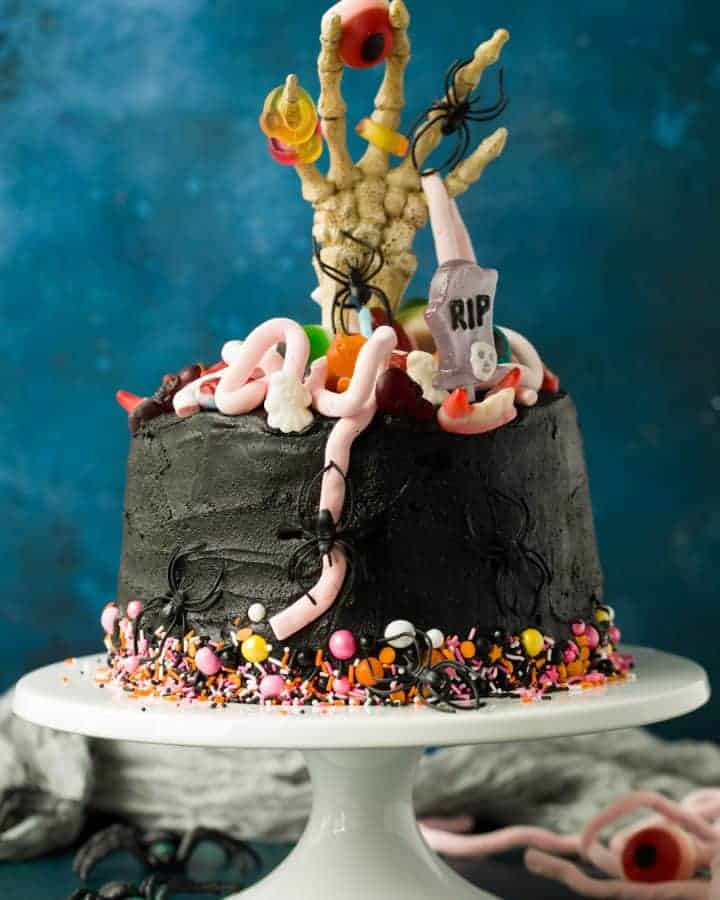 A 5 layer chocolate cake covered with black buttercream. There are colourful sprinkles around the bottom of the cake and a skeleton hand sticking out from the middle. The top of the cake is decorated with Halloween sweets.