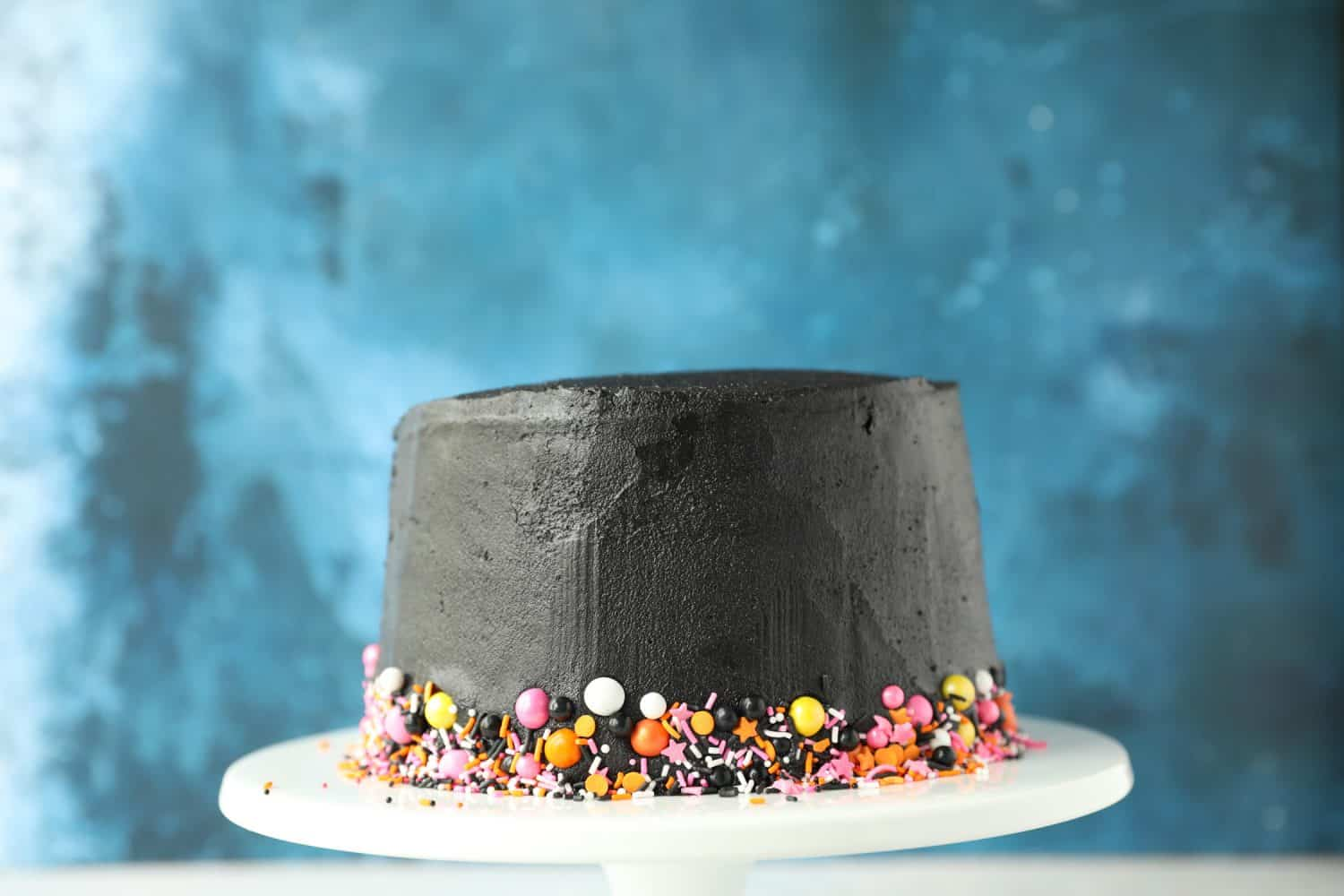 a black cake with colourful sprinkles around the bottom border of the cake.