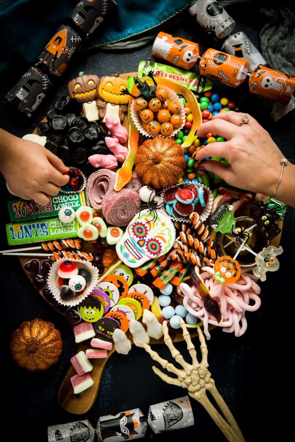 A round board covered with Halloween sweets, candy and chocolates. There is a child's hand reaching in from the left, an adult's hand reaching in from the right and a fake skeleton hand reaching in to the bottom of the board.