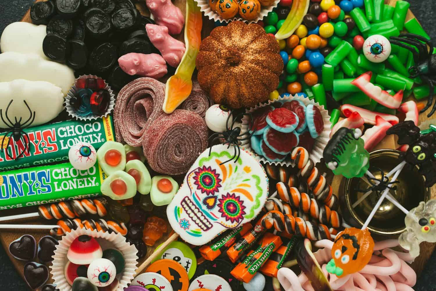 Close up of lots of different Halloween candy. There is a large marshmallow day of the dead lolly in the centre and it is surrounded by lollipops, chocolate and sweets.
