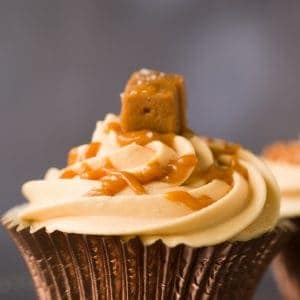 Profile of a salted caramel cupcake in a rose gold cupcake case. There is icing on top of the cupcake and a piece of fudge.