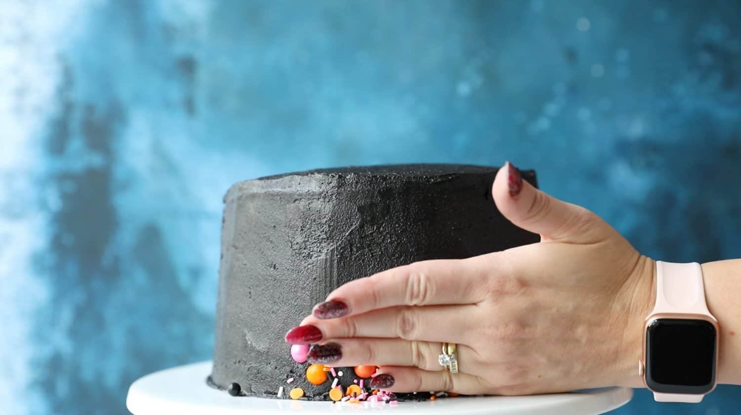 Pressing sprinkles into the side of a black cake.