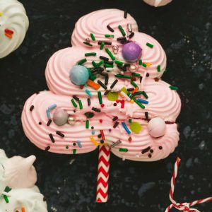 A Chrismas tree made from meringue it's covered in sprinkles and has a red and white straw poking beneath it.