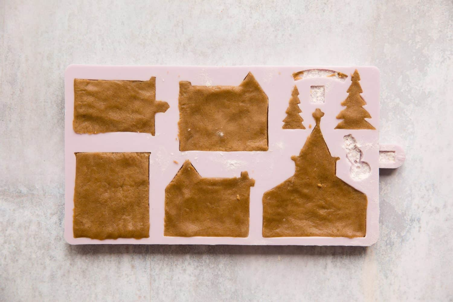 A gingerbread mould that has gingerbread dough pressed into it.