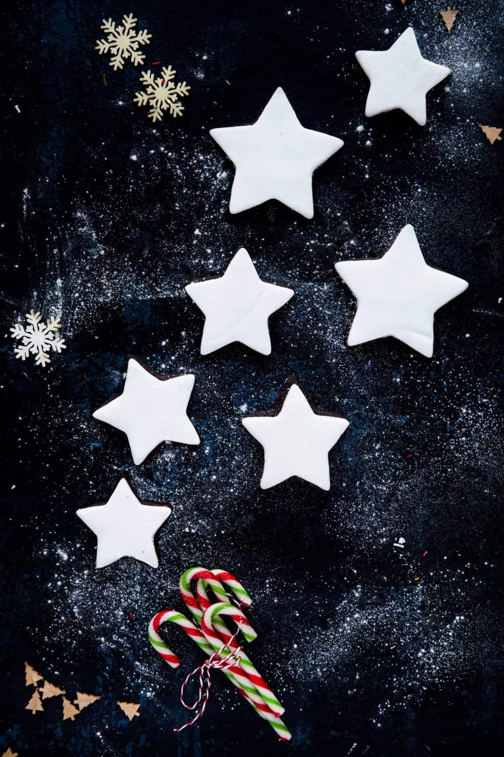 Overhead view of star shaped chocolate biscuits that have been covered in white fondant icing.