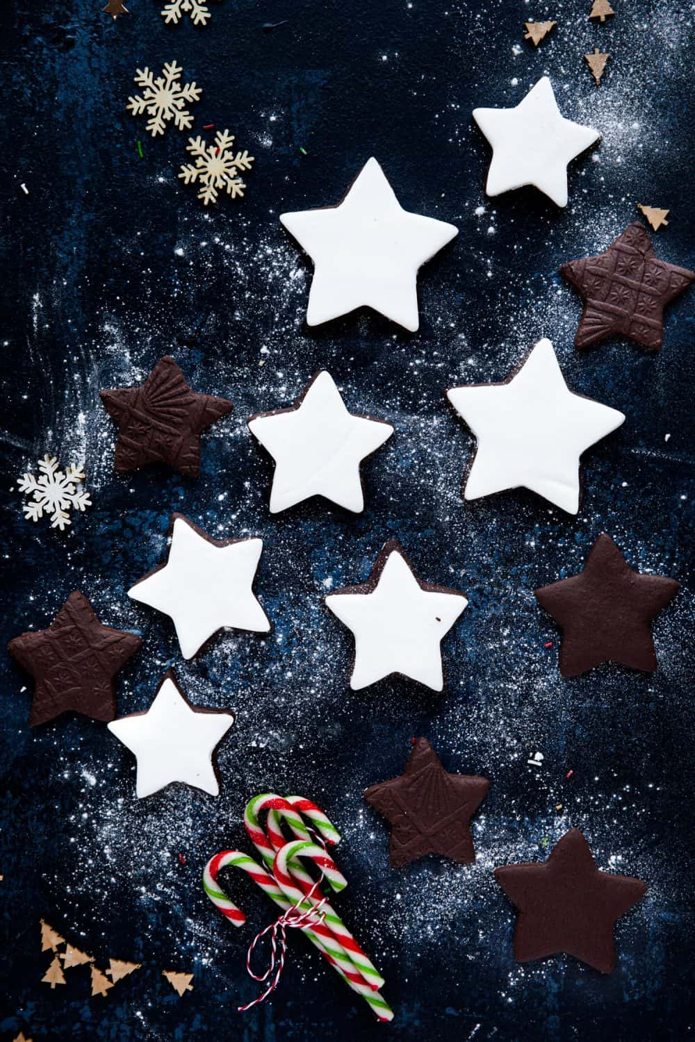 A selection of chocolate biscuits in star shapes. Some are plain and others have been covered in white fondant icing.