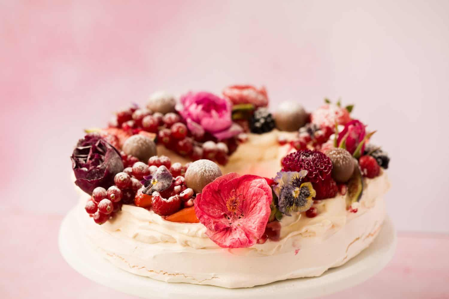 3/4 angle of a circular pavlova that has been decorated with fruit and edible flowers.