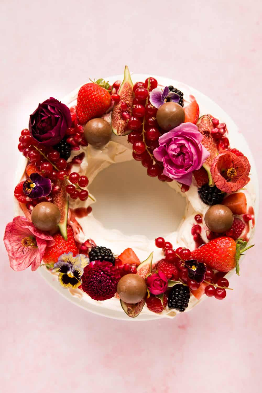 A pavlova topped with whipped cream, fresh fruit and edible flowers.