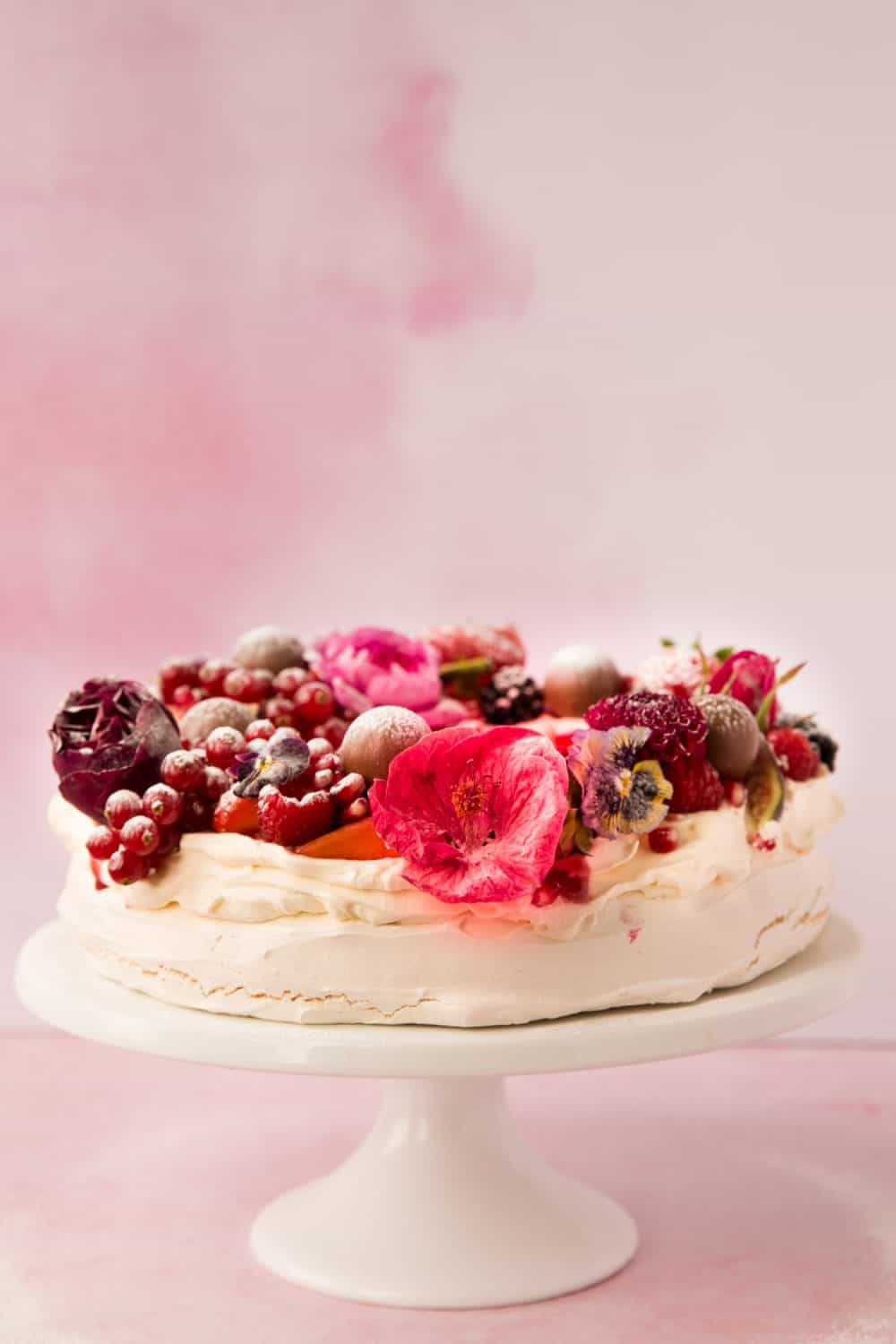 A pink background with a pavlova dessert on a white cake stand. The pavlova is covered with cascading berries and topped with chocolates and pink and red edible flowers.