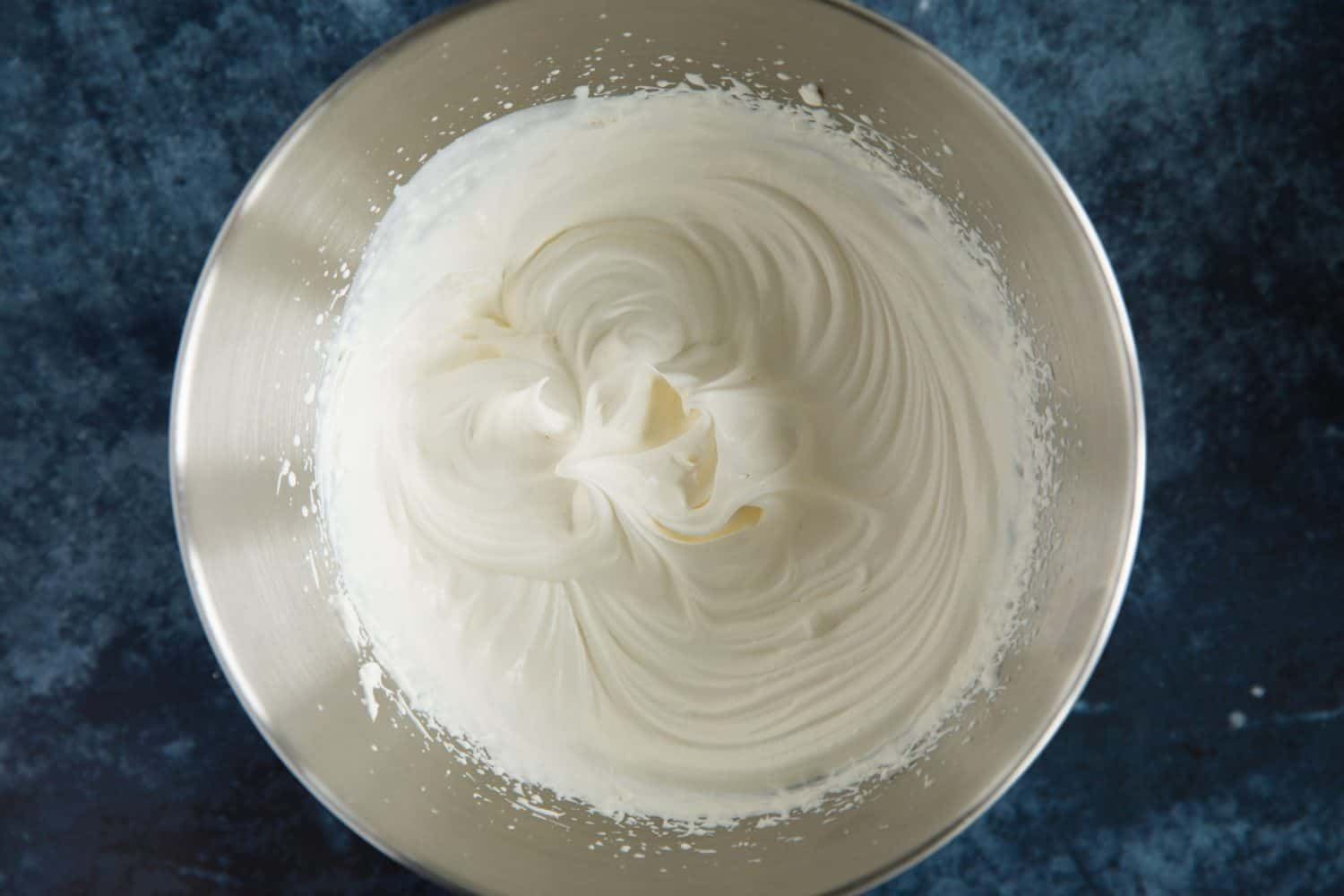 A silver mixing bowl containing whipped double cream.