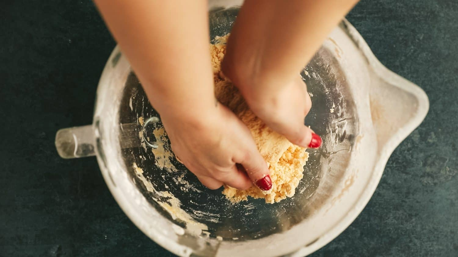 A mixing bowl with hands reaching in to knead dough.