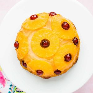 Overhead view of a pineapple upside down cake on a white plate