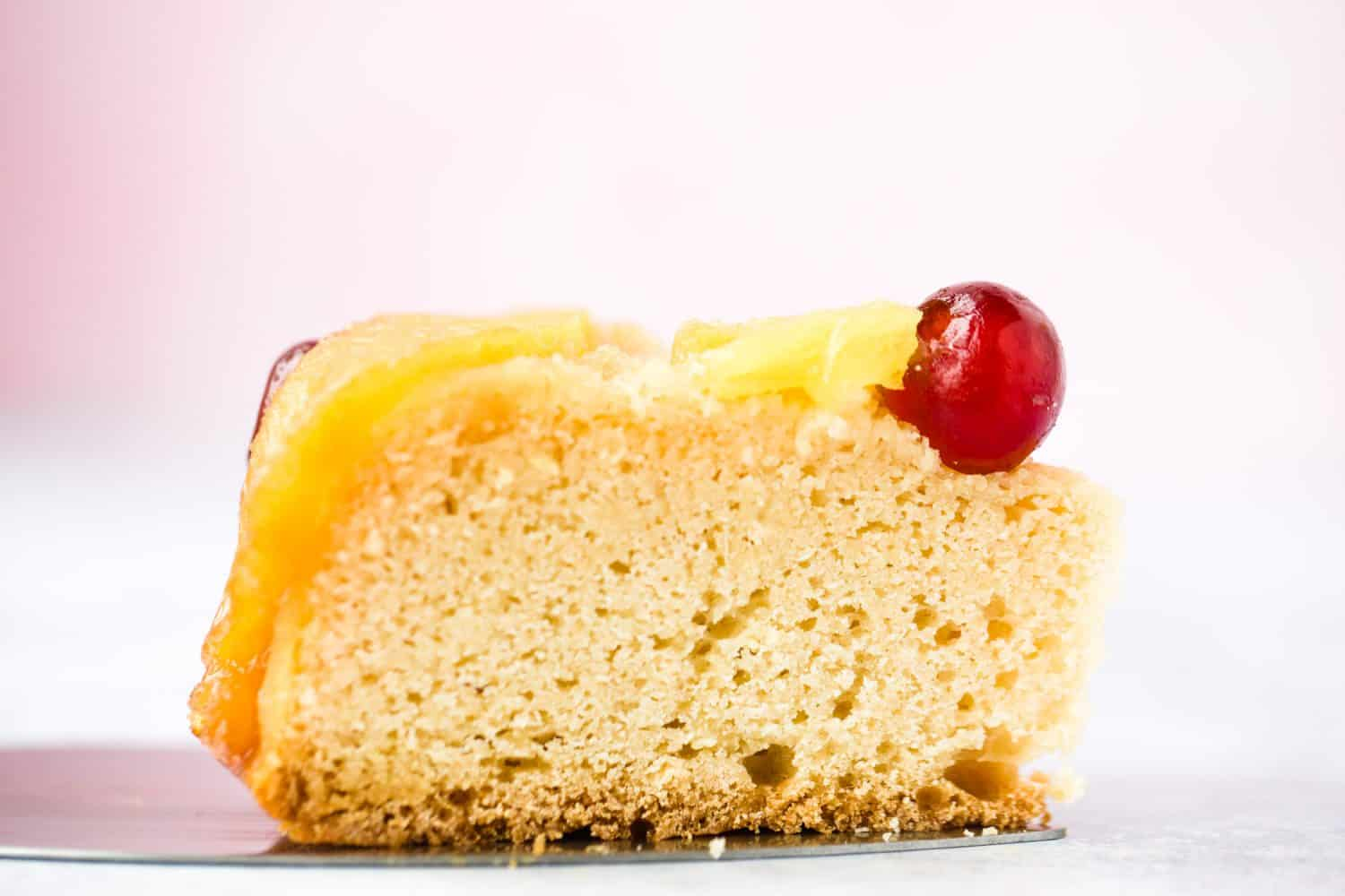 Side profile of a piece of sponge cake with pineapple and a cherry on top.