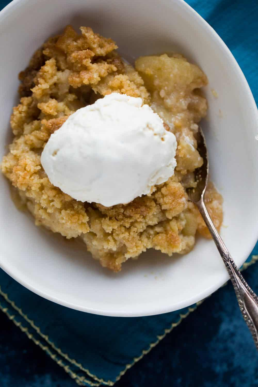 A white bowl with apple crisp inside and a scoop of ice cream on top.