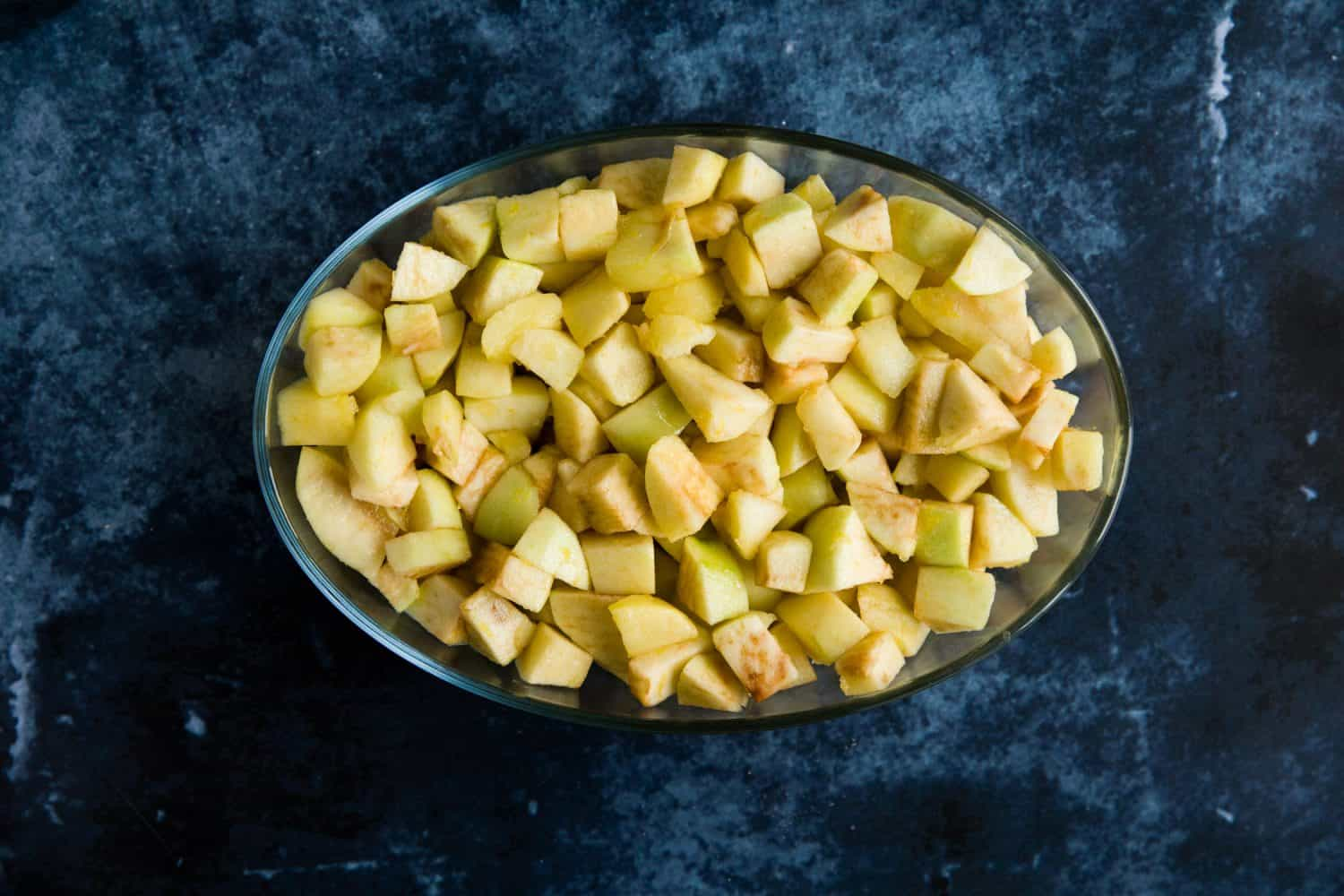 A pyrex dish with cut up bramley and golden delcious apples inside.