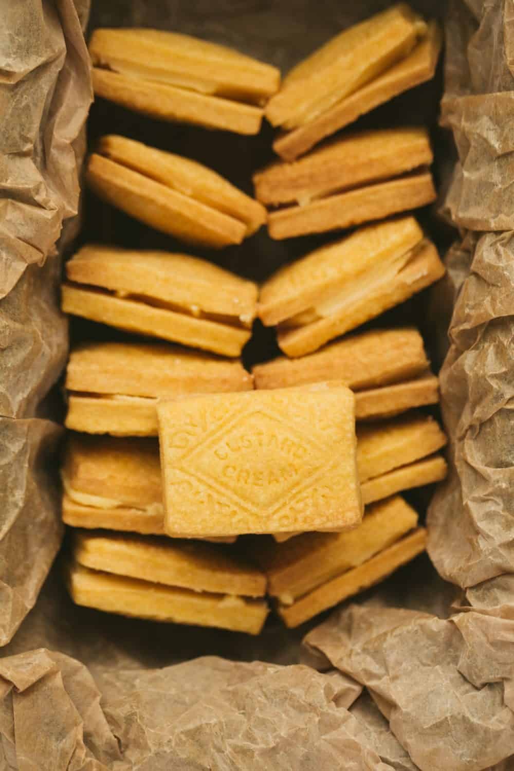 A baking tin lined with brown paper with two rows of custard cream biscuits.
