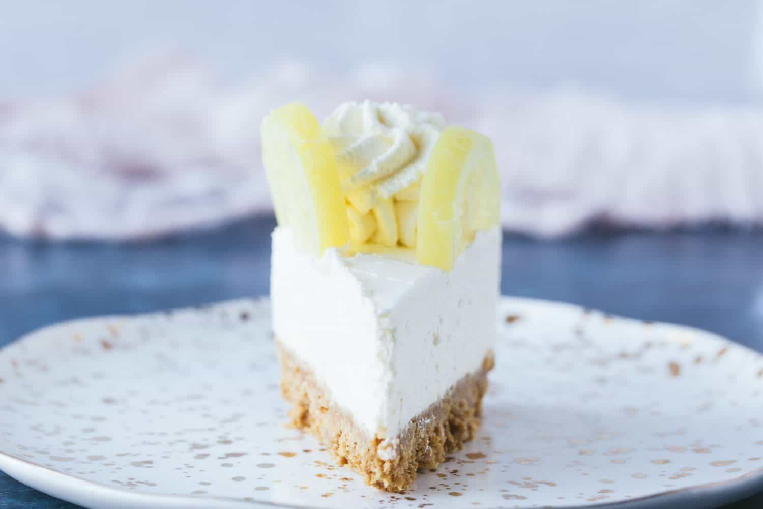 A single slice of lemon cheesecake on a small dessert plate.