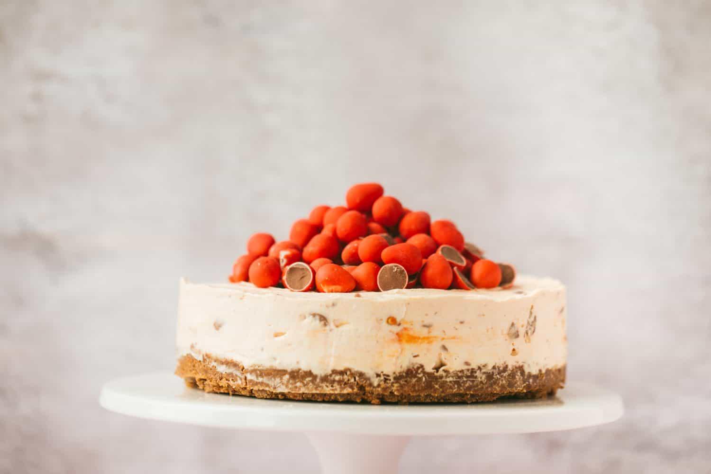 A mini egg cheesecake on a white cake stand.