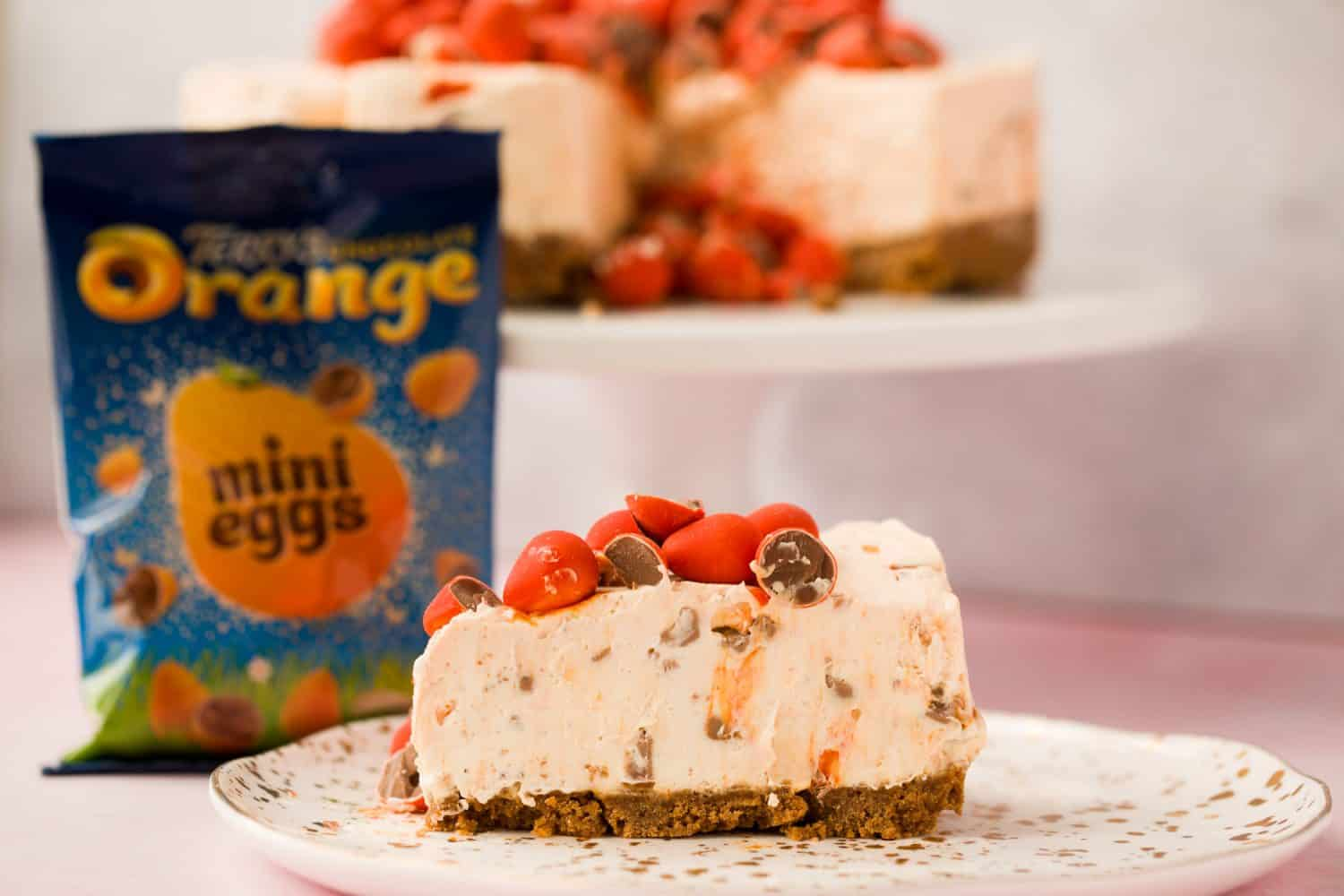In the foreground a slice of cheesecake topped with orange mini eggs, beside the cake is a bag of Terry's mini eggs.