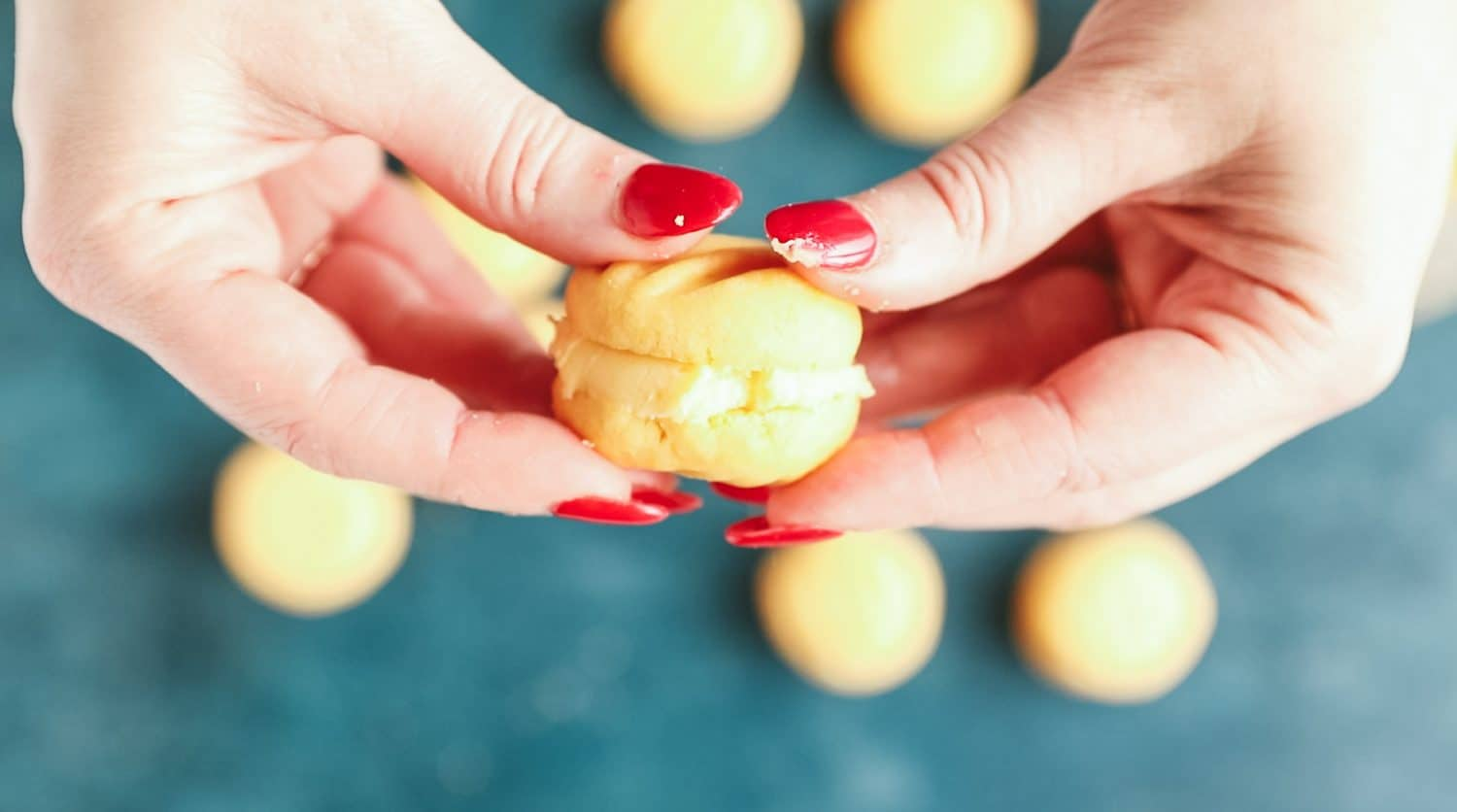 Hands sandwiching together two halves of biscuit that have been spread with buttercream.