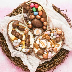 Three Easter eggs filled with cheesecake in an Easter nest.