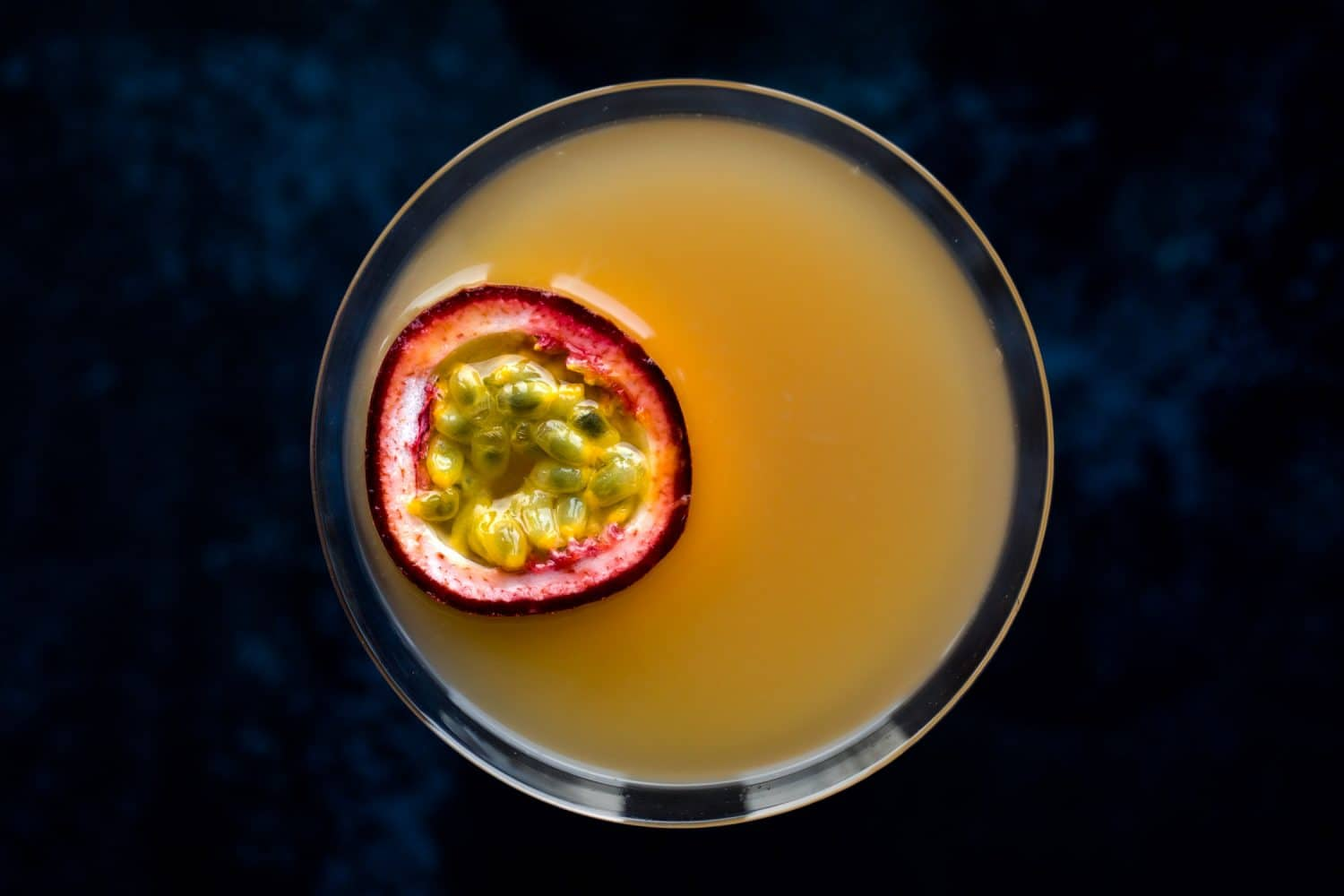 Overhead view of a passion fruit martini with a piece of passion fruit for garnish.