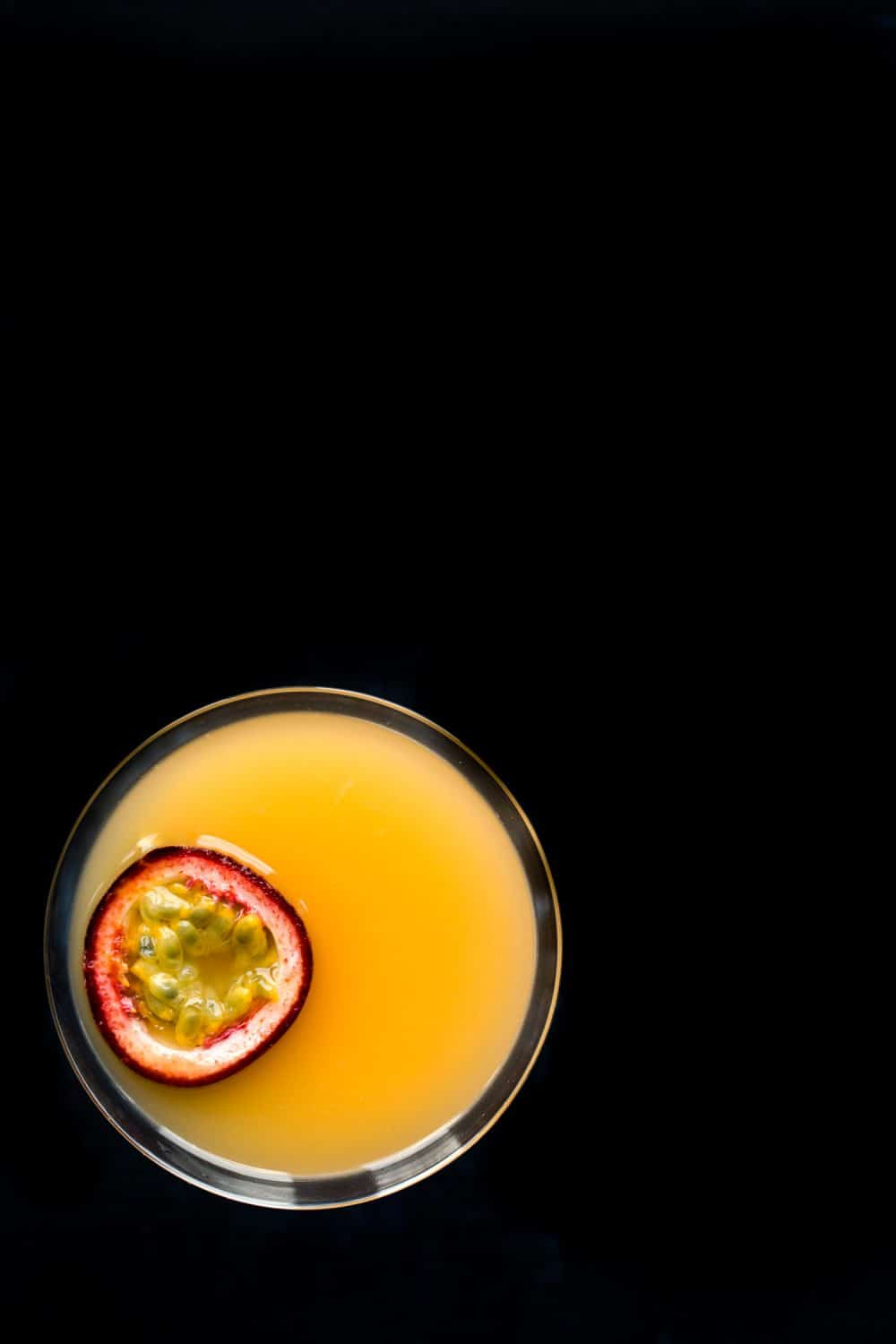 Bird's eye view of a martini glass on a very dark background. The drink inside the glass is orange and there is a slice of passion fruit on top of the drink.