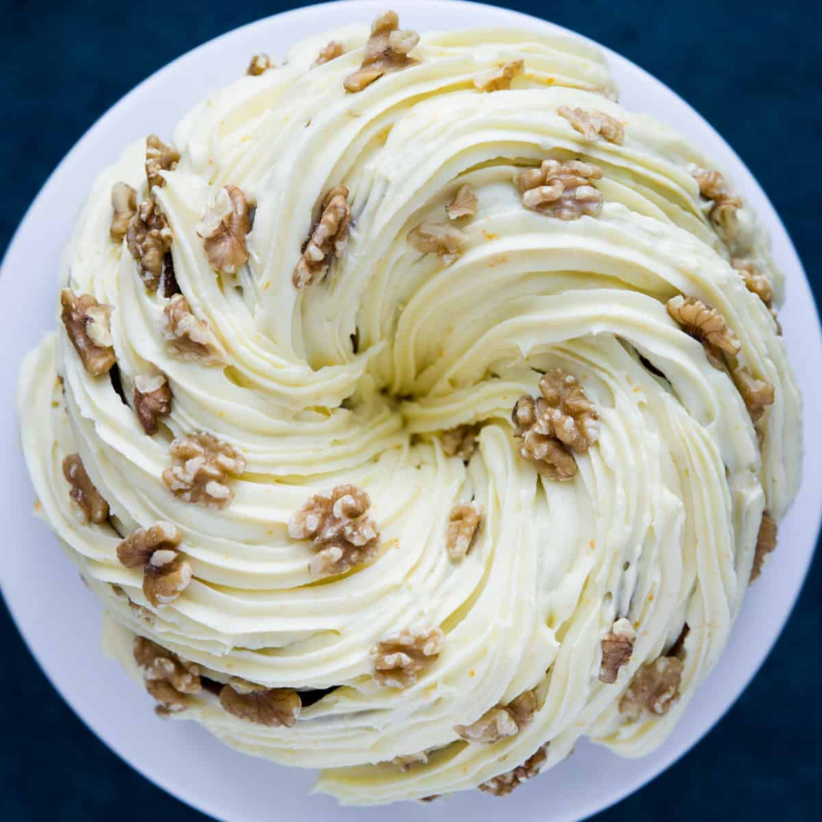 A carrot cake bundt that has been covered in a cream cheese frosting with walnuts.