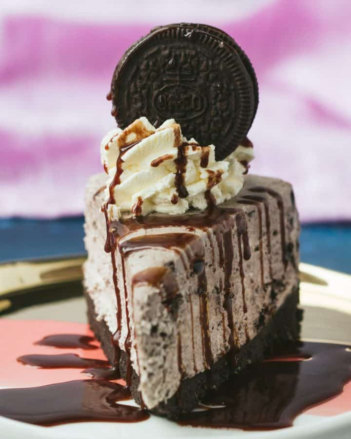 A slice of Oreo Cheesecake that has been drizzled with chocolate sauce.