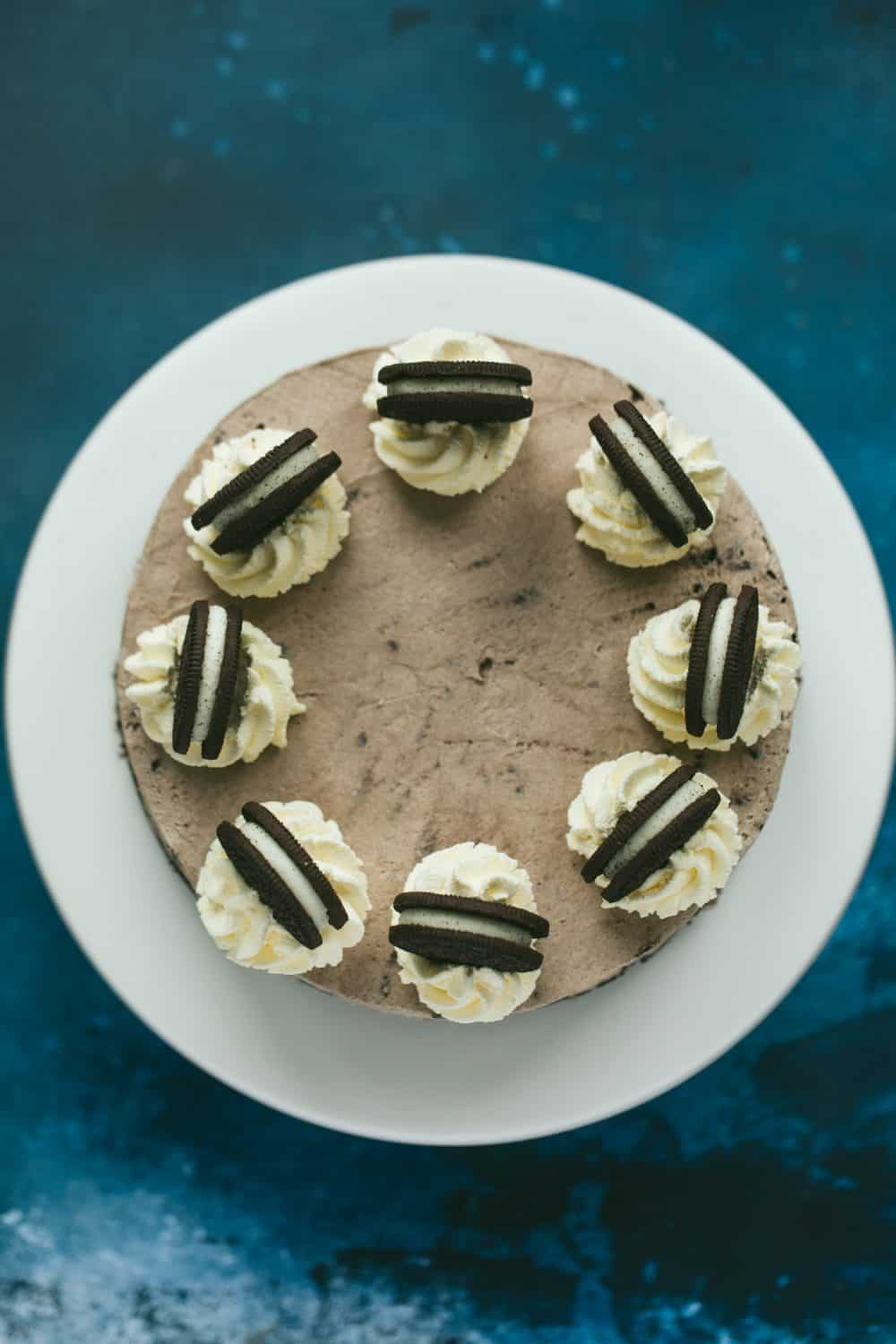 Overhead of a dessert on a cake stand. There is a dark blue background.