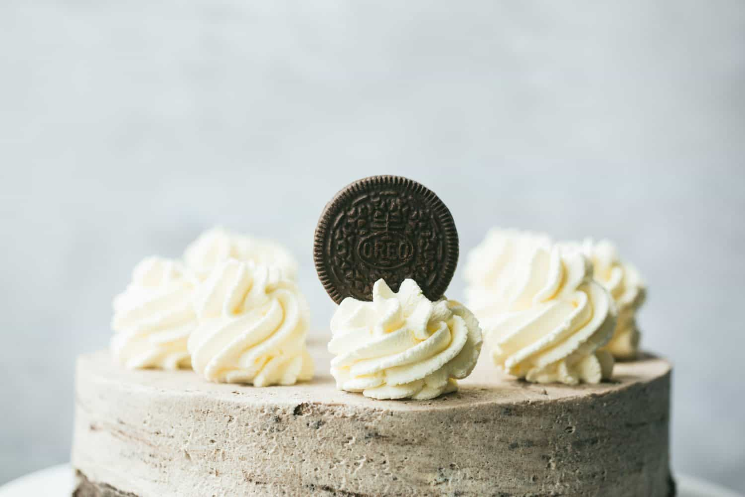 Side view of a cheesecake with swirls of homemade whipped cream on top and one Oreo cookie.