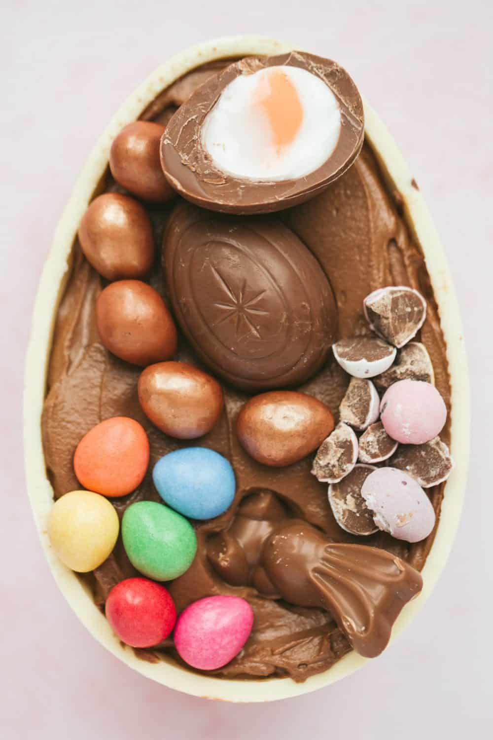 A white chocolate egg filled with chocolate cheesecake and colourful mini eggs.