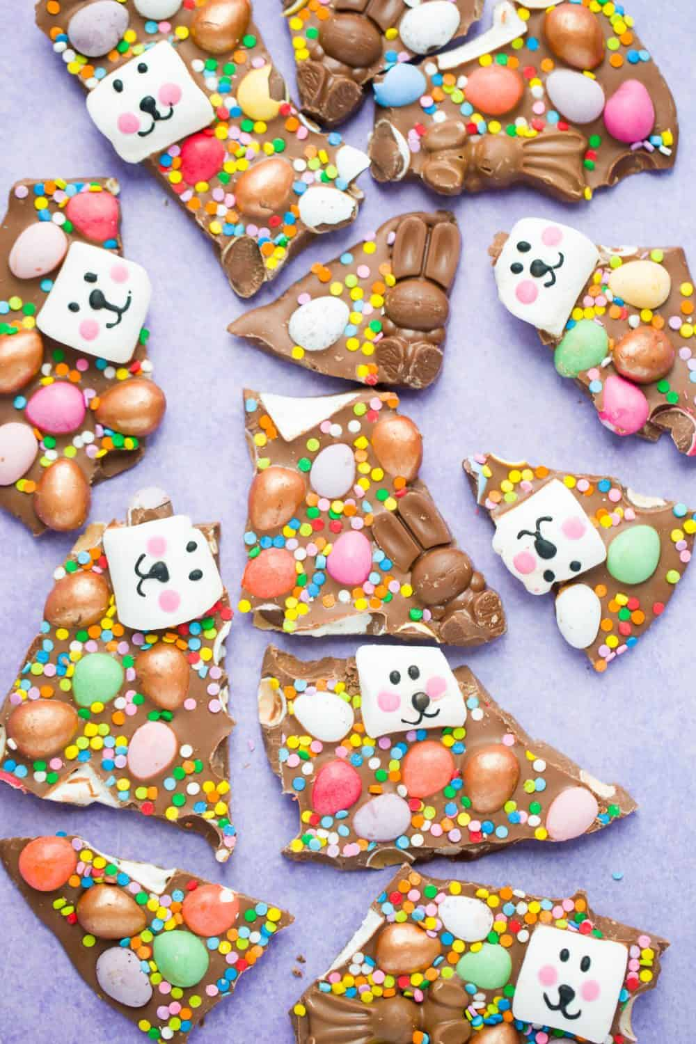 chocolate bark broken into pieces  topped with Easter treats on a purple background.