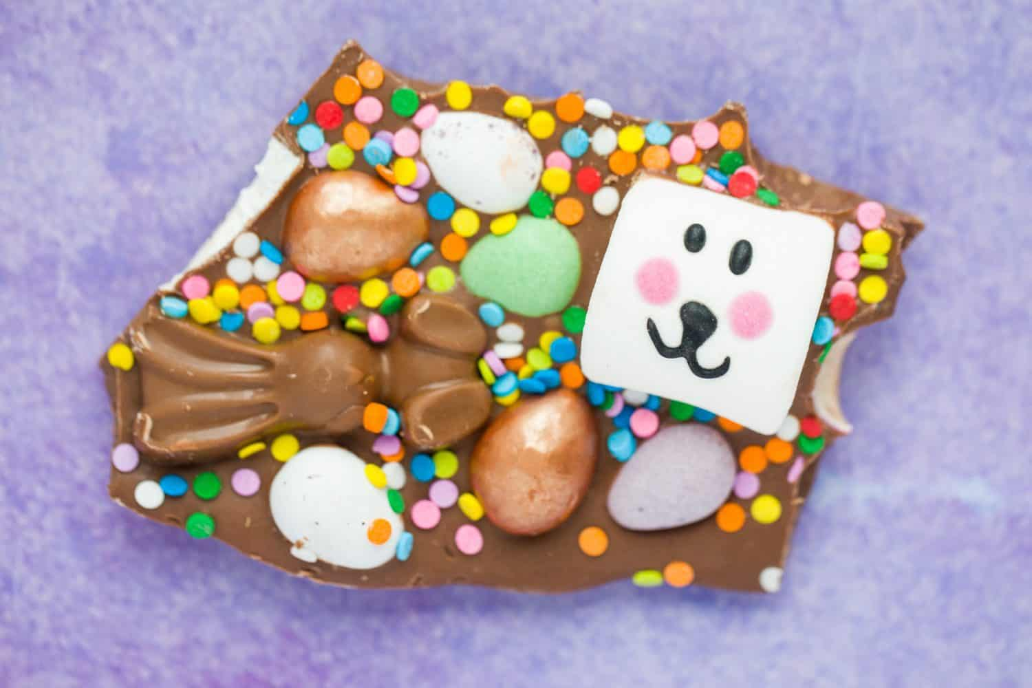 A piece of chocolate with a malteser bunny, mini eggs and a marshmallow bunny.