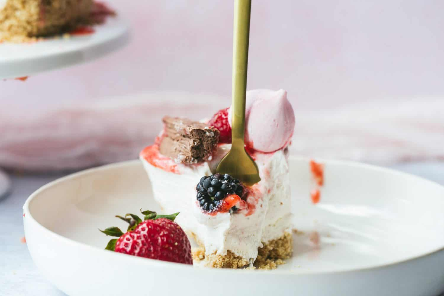 A slice of strawberry and cream cheesecake with a fork sticking into it.