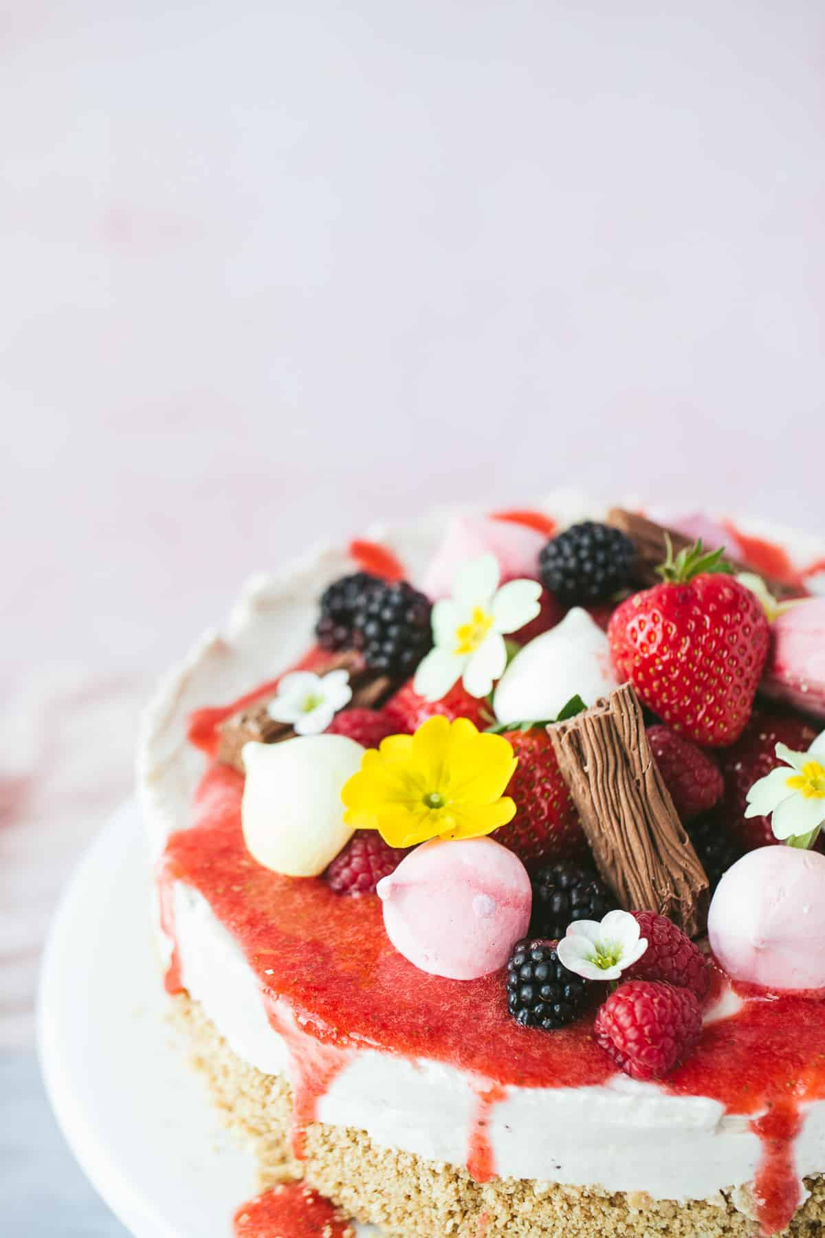 An Eton Mess Cheesecake covered with fruit coolis, mini meringues, chocolate flakes and edible flowers.