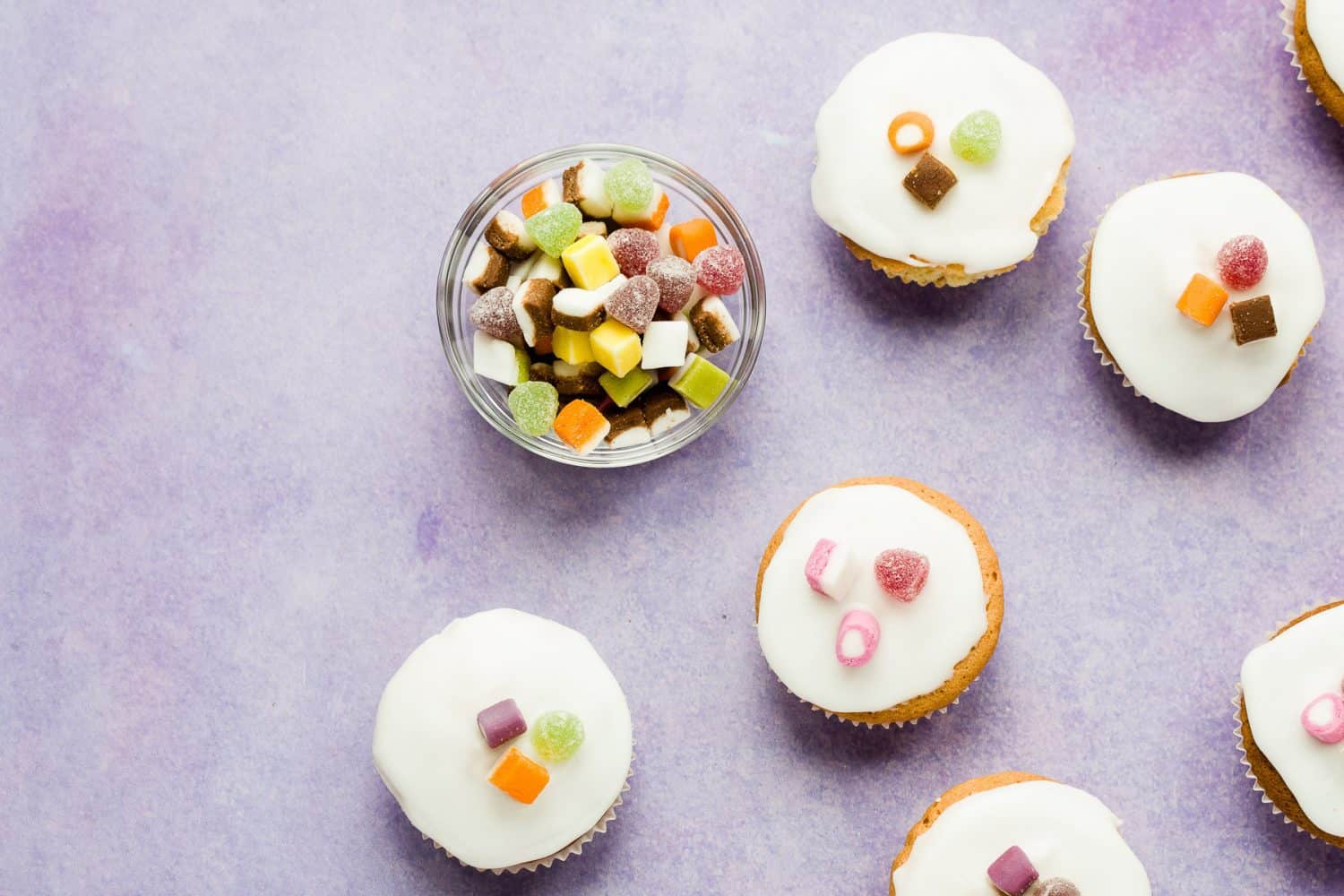 A bowl of dolly mixture next to some cake buns.