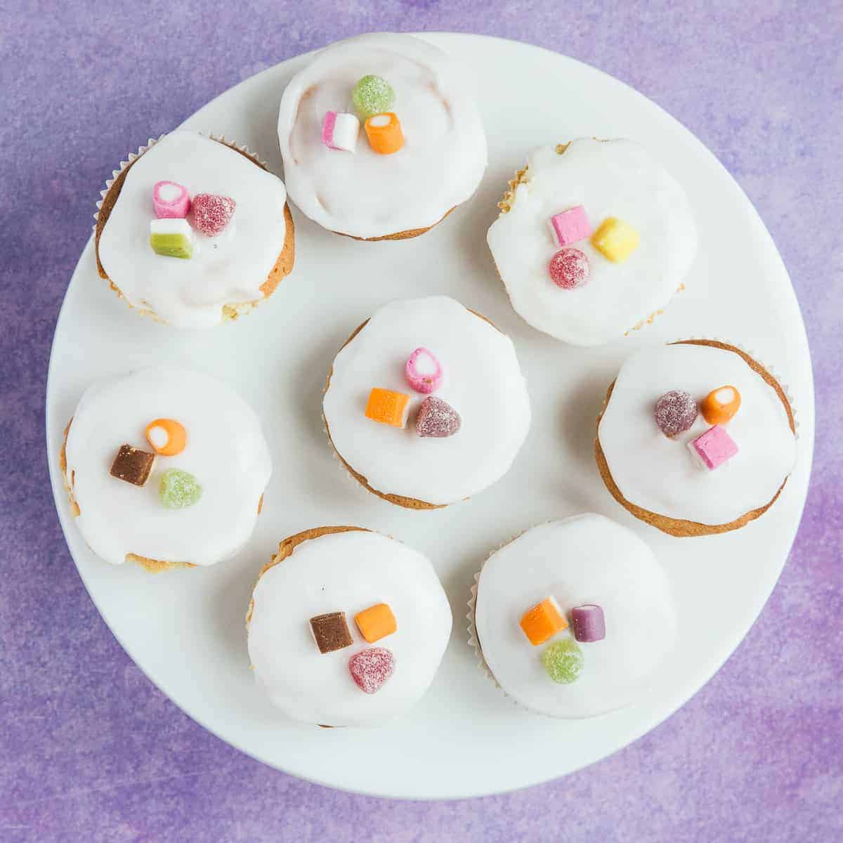 A white plate with 8 fairy cakes on top.