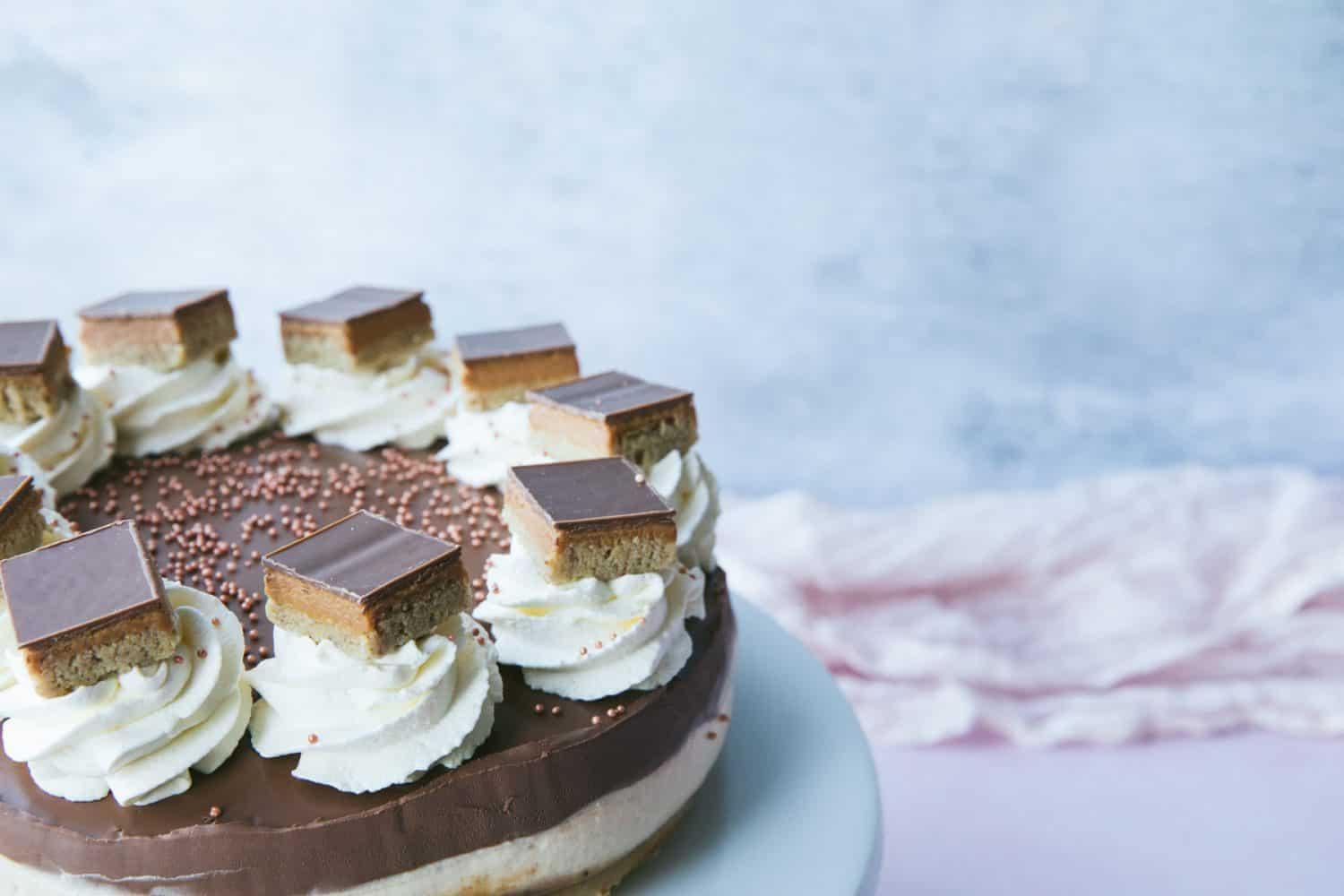 A cheesecake with shortbread, caramel, filling and chocolate layers all visible.
