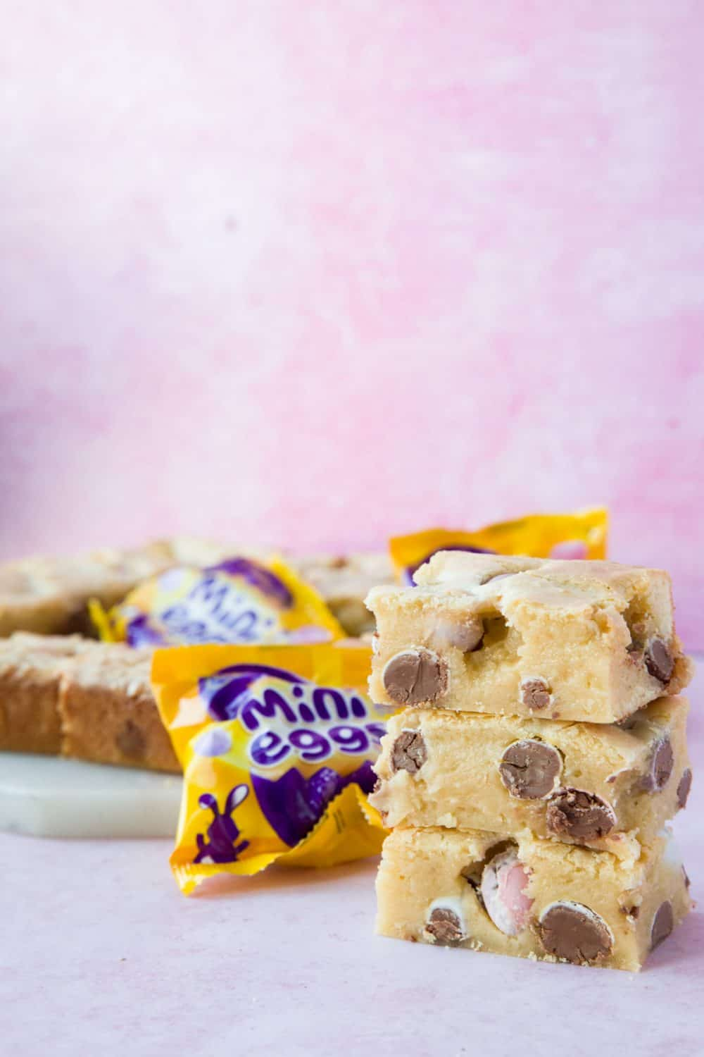 A stack of mini egg blondies with a yellow packet of Cadbury mini eggs to the side.
