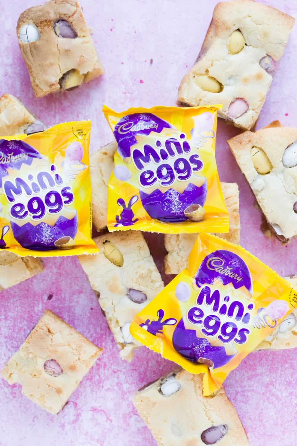 Slices of mini egg blondies with packets of Cadbury.
