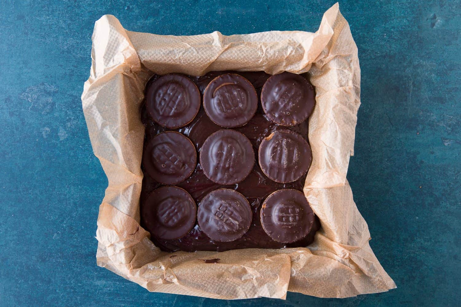 Brownie mixture in a square tin topped with 9 jaffa cakes.