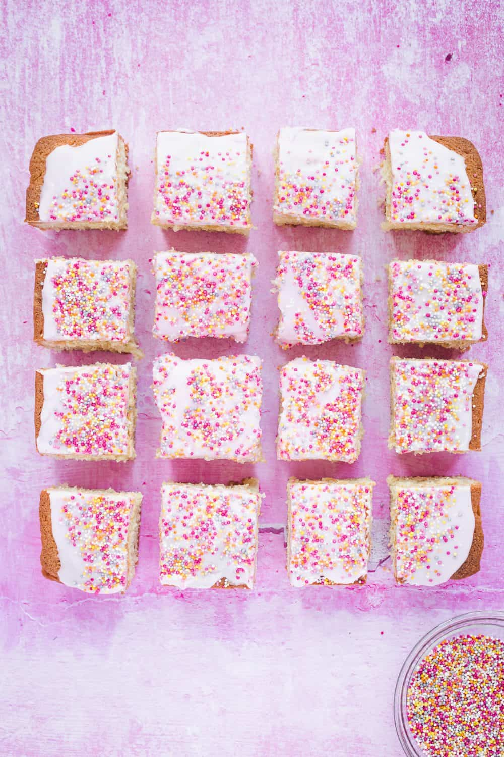 Tottenham Cake cut into squares on a pink background with a bowl of hundreds and thousands.